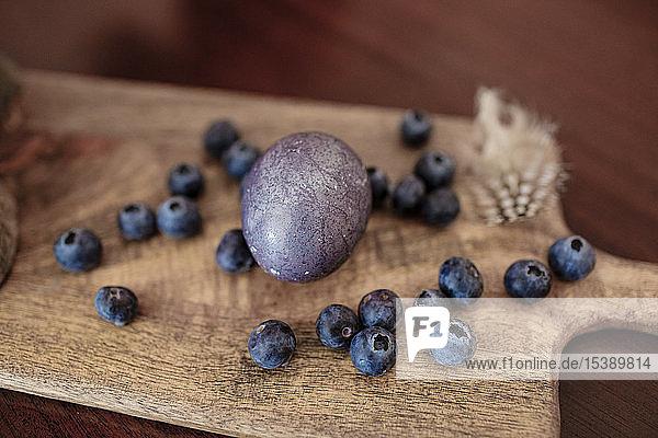 Gefärbtes Osterei  Blaubeeren und eine Feder auf Holzbrett