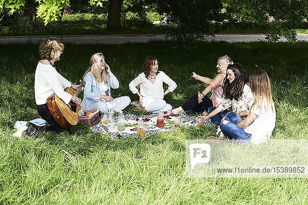 Frauengruppe mit Gitarre amüsiert sich bei einem Picknick im Park