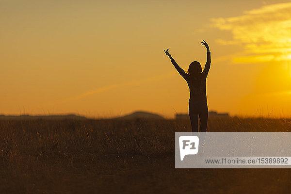 Frau geht bei Sonnenuntergang in der Natur spazieren