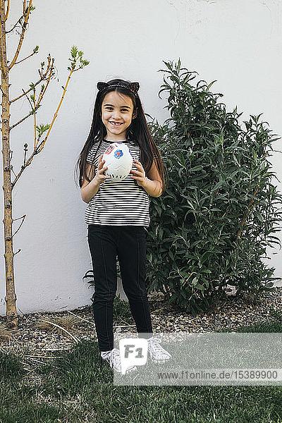 Mädchen hält bemaltes Osterei im Garten