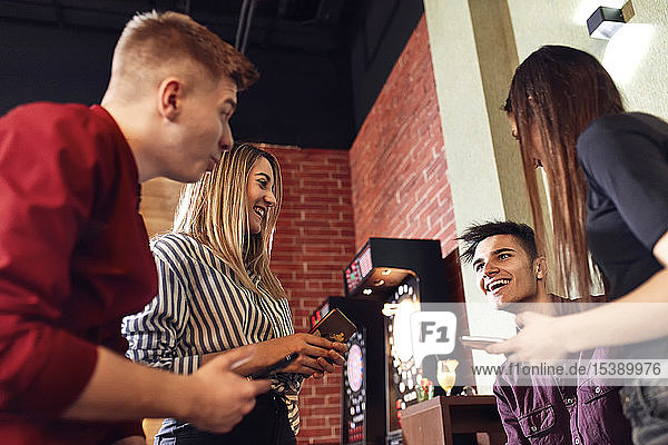 Happy friends with smartphones socializing in a bar