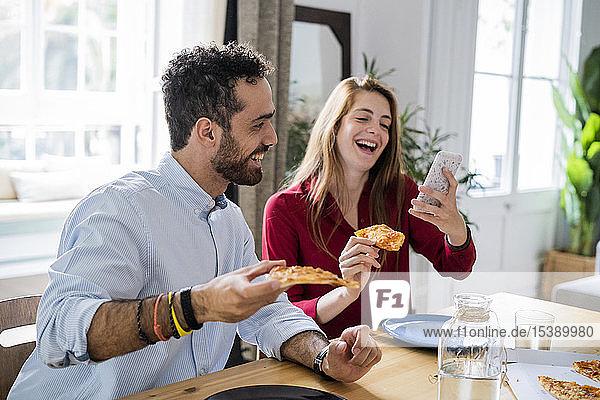 Freunde haben Spaß  essen Pizza  benutzen Smartphone