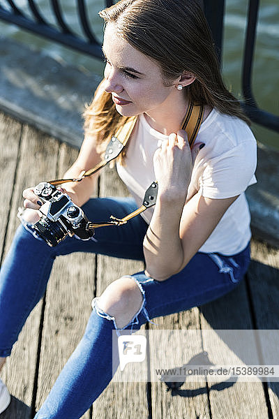 Junge Frau erkundet New York City und fotografiert an der Brooklyn Bridge