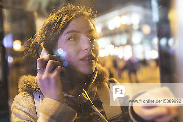 Spain  Madrid  young woman in the city using a phone box