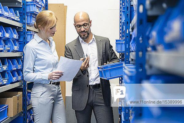Geschäftsmann und Geschäftsfrau untersuchen Werkstück in Fabriklagerhalle