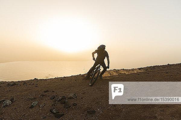Spanien  Lanzarote  Mountainbiker auf einer Fahrt an der Küste bei Sonnenuntergang