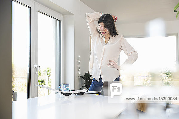 Young woman standing at table at home looking at plane model