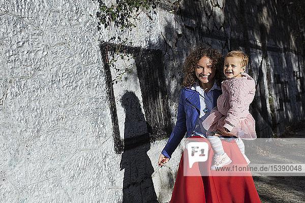 Porträt einer glücklichen Mutter  die ihre Tochter an einer Steinmauer trägt