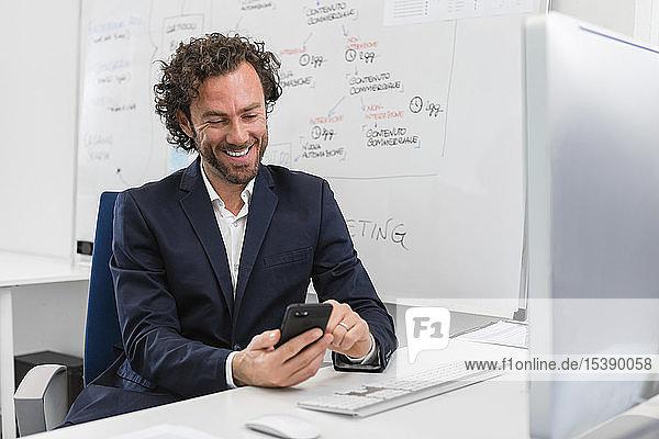 Lächelnder Geschäftsmann sitzt am Schreibtisch im Büro und benutzt sein Handy