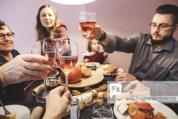 Familie beim gemeinsamen Abendessen klirrende Weingläser