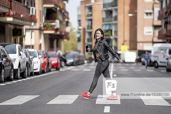 Junge Frau  die den Fußgängerüberweg überquert und ein Mobiltelefon benutzt