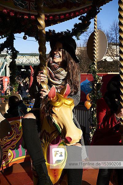 Happy woman having fun on a carousel