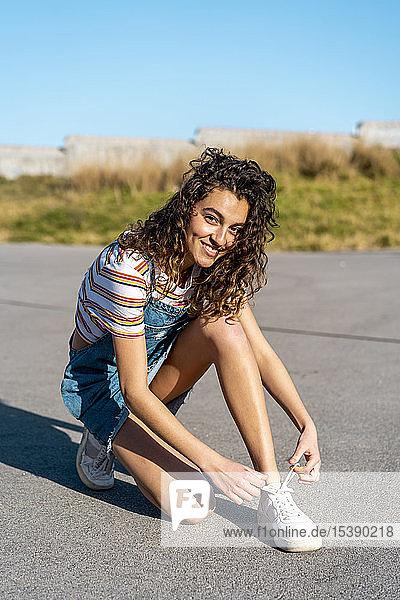 Junge Frau sitzt auf dem Boden und bindet Schuhe