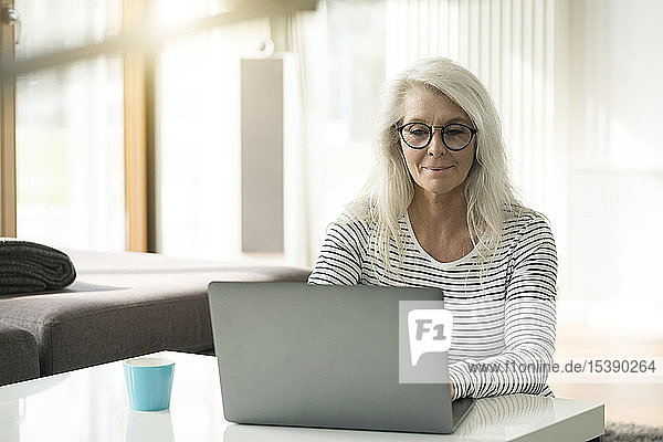 Portrait of mature woman using laptop at home