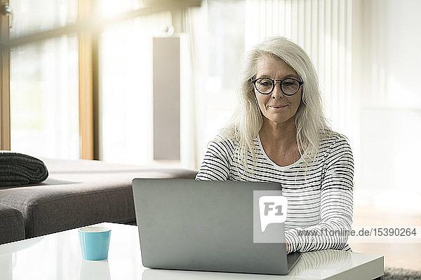Portrait einer reifen Frau  die zu Hause einen Laptop benutzt