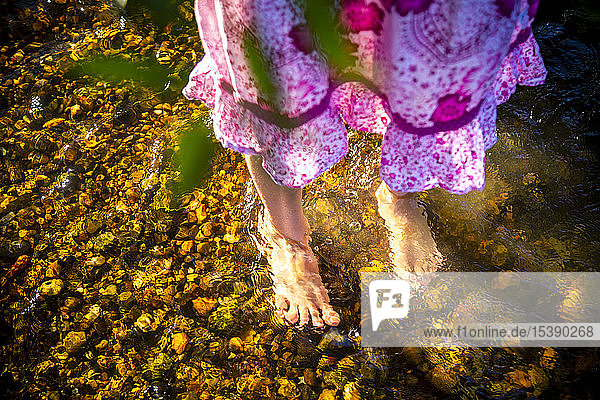 Feet of girl standing in a brook