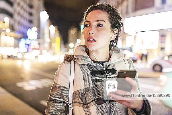 Spanien  Madrid  junge Frau in der Stadt  die nachts ihr Smartphone benutzt und Kopfhörer trägt