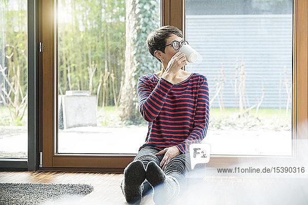 Frau sitzt auf dem Boden vor der Terrassentür und trinkt Kaffee