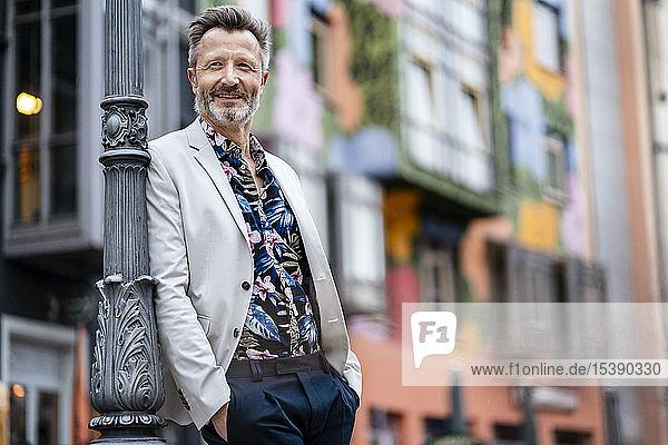 Porträt eines modischen  reifen Mannes mit grauem Bart  der sich anlehnt