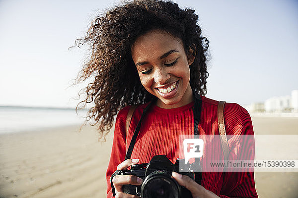 Smiling young woman looking at camera on the beach