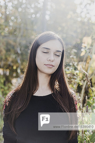 Portrait of woman with closed eyes in urban garden