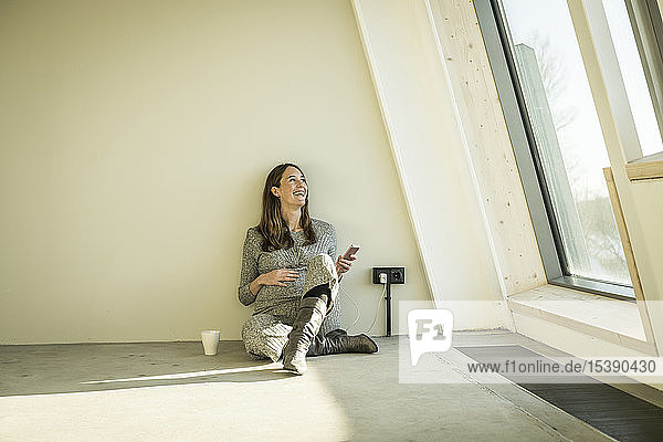 Pregnant woman drinking tea  sitting on floor of her new home