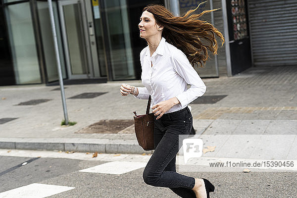 Businesswoman running in the street