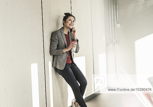 Lächelnde Geschäftsfrau lehnt im Büro an einer Wand und telefoniert mit dem Handy