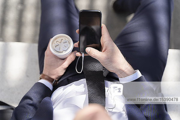 Close-up of businessman with takeaway coffee and smartphone outdoor