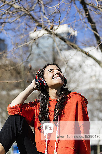 Young contemporary dancer wearing red hoodie shirt  sitting and listening to music