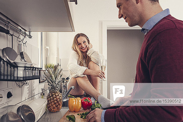 Young couple in kitchen cooking and drinking champagne