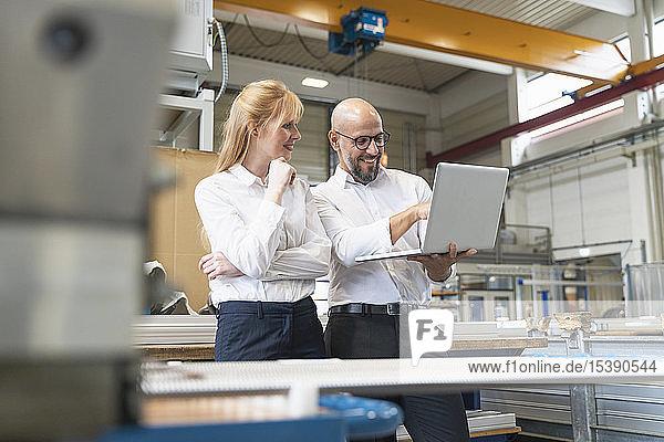Lächelnder Geschäftsmann und Geschäftsfrau mit Laptop in der Fabrik