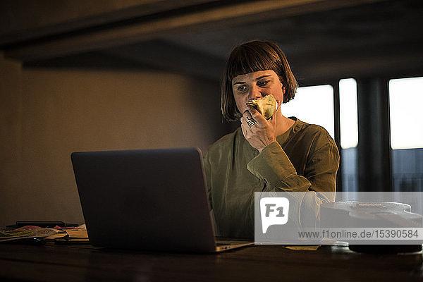 Geschäftsfrau arbeitet spät  isst Apfel