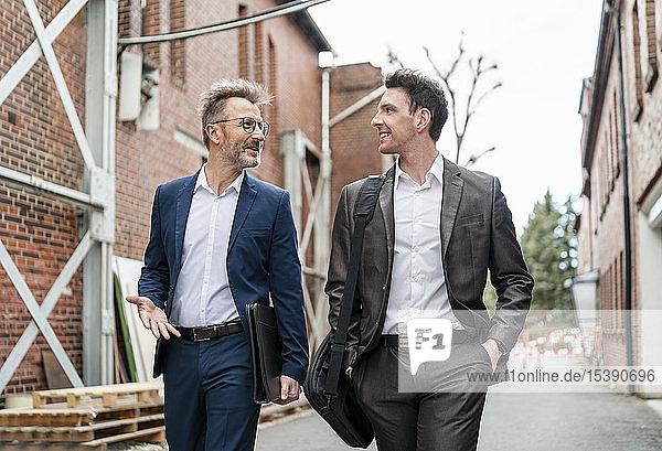 Zwei lächelnde Geschäftsleute gehen und unterhalten sich an einem alten Backsteingebäude