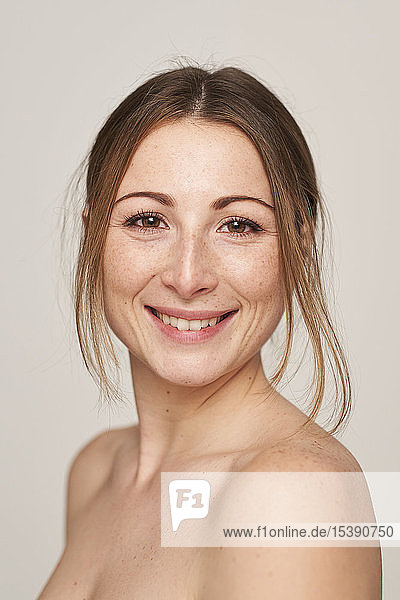 Porträt einer lächelnden schönen jungen Frau mit Sommersprossen