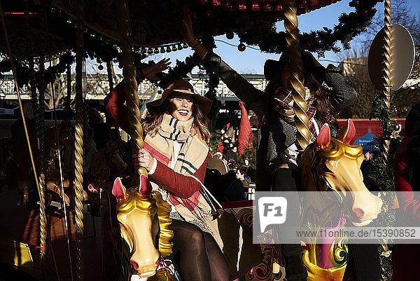 Two happy women having fun on a carousel