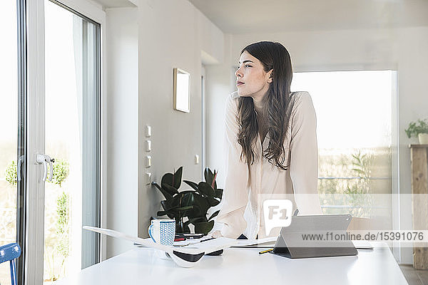Young woman standing at table at home looking sideways