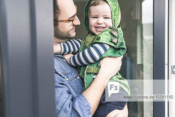 Father carrying happy son in a costume at terrace door at home
