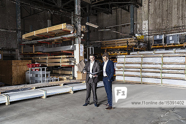 Two businessmen with folder talking in an old storehouse