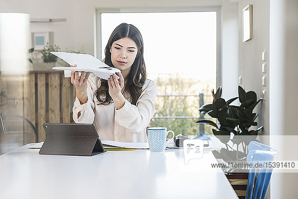 Young woman sitting at table at home holding plane model