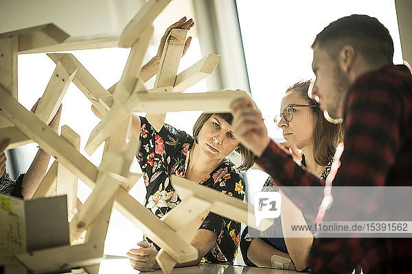 Group of creative professionals building wood object for a project