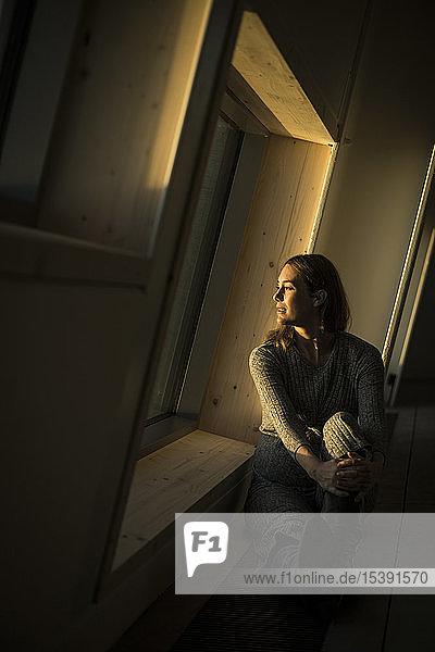 Frau sitzt bei Sonnenuntergang am Bürofenster  Porträt