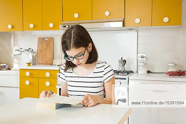 Mädchen liest ein Buch in der Küche
