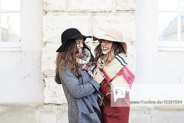 Two happy playful women wearing floppy hats