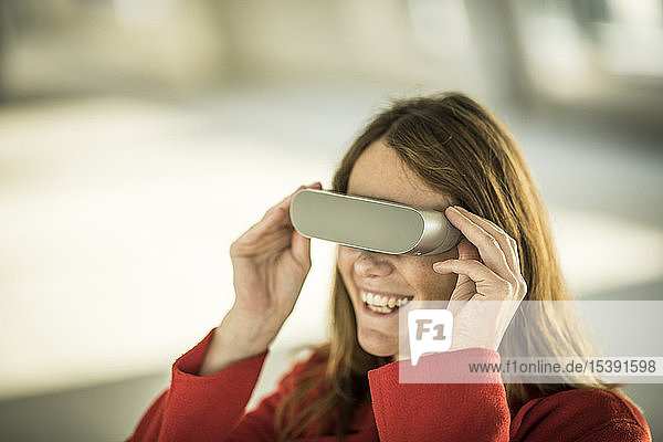 Smiling businesswoman looking through VR goggles