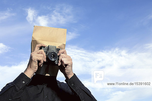 Man with paper bag above his head taking a picture
