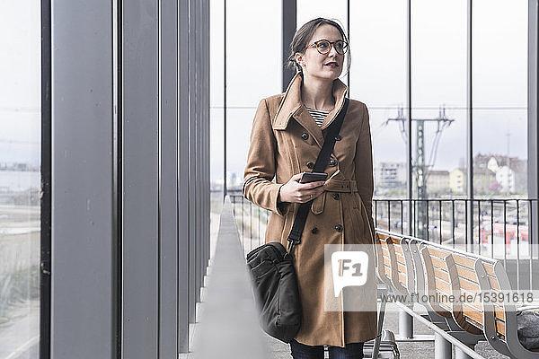 Lächelnde Geschäftsfrau geht mit Gepäck und Handy