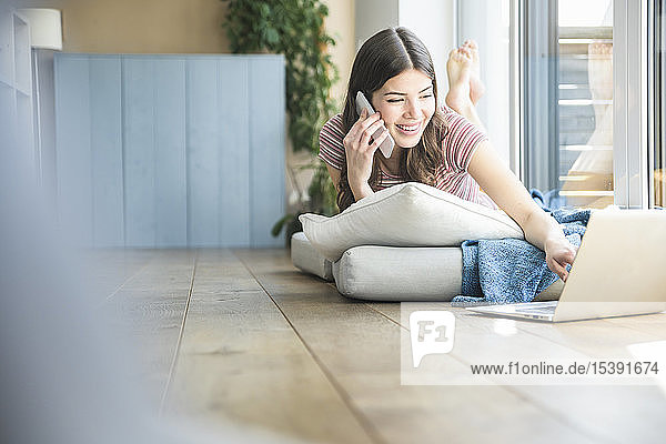 Young woman lying at the window at home using cell phone and laptop