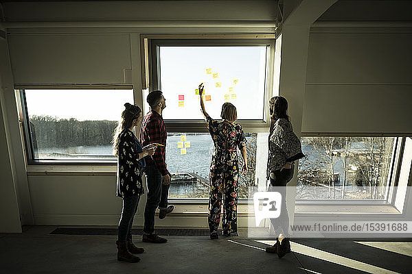 Kreatives professionelles Stehen im Büro  Brainstorming  Haftnotizen an ein Fenster kleben