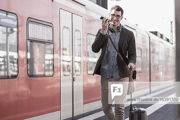 Glücklicher junger Mann mit Handy auf Bahnsteig entlang des S-Bahnsteigs